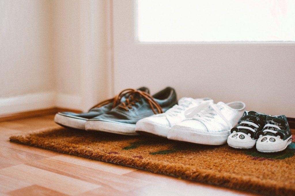 trois paires de chaussures posées sur tapis à l'entrée d'un logement